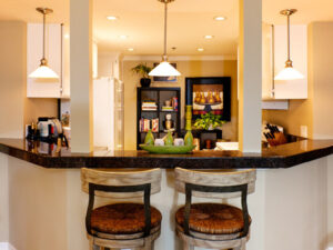 After: Transitional interior design - Swivel bar stools, granite counter tops, modern glass pendent lights