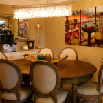 Cameo back dining chairs, contemporary wall art, modern crystal chandelier, transitional interior design and furniture.