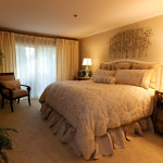 Damask bedding ensemble on a fully upholstered headboard, silk traverse over drapery with sheers, 3 dimensional tree wall art create a transitional interior design with exceptional furniture.