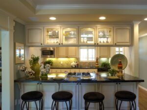 Custom antique white cathedral top cabinetry with double glass doors, iron knobs, black soapstone countertops, iron bar stools, recessed ceiling with crown molding, pilaster and header millwork.