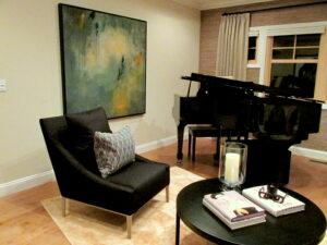 Baby grand piano, grass cloth wall covering with custom natural club drapery on iron traversing hardware and armless lounge chair punctuate the modern interior design with elegant furniture.