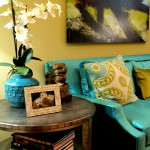 Modern work of art, turquoise and gold fabric accent pillows on torquise box arm sofa, zinc wrapped side table. This exemplifies transitional interior design using modern furniture.