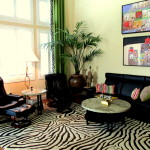Zero gravity leather chairs, zebra area rug, modern works of art, black leather fully aniline sofa, multi colored accent pillows. Transitional interior design with modern furniture.