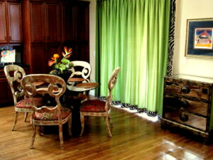 lime drapery body with zebra trimmed boarders, mirrored front chest of drawers, distressed scrolled back dining chairs.