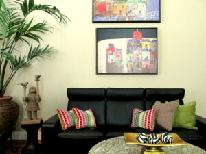 Modern works of art, black leather fully aniline sofa, multi colored accent pillows.