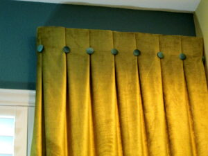 Gold fabric with turquoise accent buttons tie in with wall color and other design elements