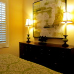 impressionistic oil on canvas, tall candle stick lamps, mahogany dresser, plantation shutters set off the transitional interior design and furniture.