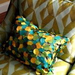 Turquoise and gold fabric accent pillow.