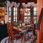 Exposed wood beams and rustic pine mill work, leaf and planter chandelier, Queen Anne dining chairs in coordinating seat covers, custom rod swag and panel window treatments, oval area rug.