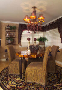 Paisley tapestry slip covered chairs with tassel trim detail, custom valance with coordinating lined cascades, plantation shutters, beaded chandelier, hand textured walls.