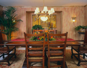 Hand textured walls and crown moulding, treacle style farm dining table, leather head chairs, preserved palm foliage.