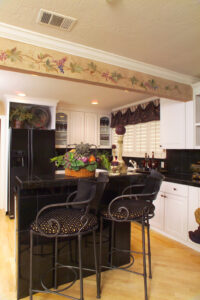 Hand painted grape vine, Cathedral raised panel white custom cabinetry, Black galaxy granite counter tops, plantation shutters, custom valance, home decor and furnishings.