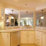 Cream custom cabinetry, transitional interior design, seeded glass cabinet doors, pillar pass-through opening.