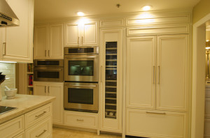 Cream custom cabinetry, high bay with stainless steel triple ovens, vertical wine refrigerator and French door refrigerator, transitional interior design,