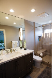 Wallnut Shaker style door cabinetry, transitional interior design, honed travertine counter top, under mount lavatory, deck mounted wide spread brushed nickel faucet and full height mirror, Glass flush mount sconces, wood grained porcelain tile floors and shower walls.