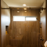 "Brushed nickel shower barn door hardware with faux cherry plank wood 15"" x 24"" porcelain tile walls, transitional interior design."