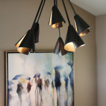 Sophisticated and elegant interior design. Hand forged iron entry chandelier and impressionistic oil on canvas.