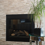 Gas log fireplace, marble off-set dimensional tile wall creates a transitional interior design.