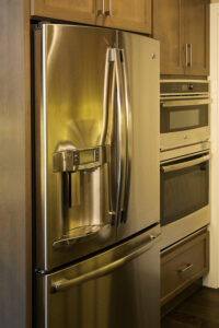 Stainless steel GE front French door refrigerator and built-in double ovens, transitional interior design.