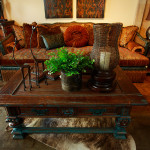 Craftsman Formal distressed cocktail table, extra deep reversible tapestry sofa with embossed leather base detail and arms, bullion fringe skirt, nail head trim, velvet bolsters and multiple accent back pillows.