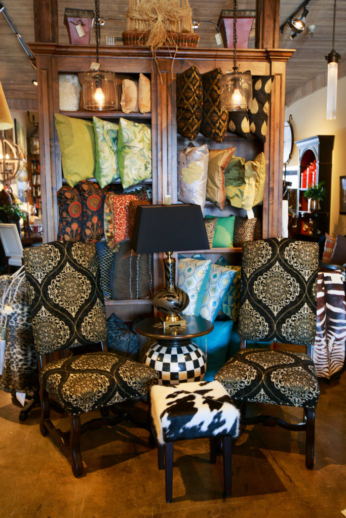 Medallion Back Side Chairs with a Nailhead Trim and Hand-Carved Noir Legs Shaded by a Collage of Accent Pillows