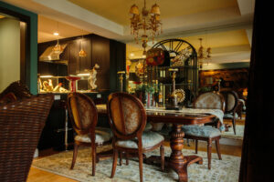 Full mirrored wall, damask print upholstered chairs and table runner, silk hand knotted area rug,