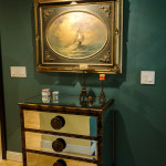 Mirror and tortoise shell finished chest of drawers and antique custom framed oil on canvas are traditional furnishing.