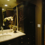 Black Traditional bowed front full height cabinetry, sculpted marble counter top, custom cocoa wall paint are element of transitional interior design.