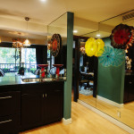 Espresso shaker style cabinet doors, stainless steel under mount double bowl sinks, verde marble counter tops, hand-blown glass pendant lights, mirrored side wall, hand blown glass decorative floral wall bowls, custom colored paint are beautiful examples of contemporary interior design.