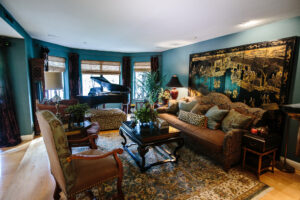 Luxurious brocade fabrics, six panel lacquer Chinese wall screen, hand knotted silk oriental rug, rich deep teal wall color and a black lacquer baby grand piano create a traditional interior design.