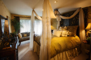 Romantic sheer swagged canopy bed, goose down comforter, leopard chaise lounge and hand painted wall mural and screen are examples of elegant furniture and romantic interior design.
