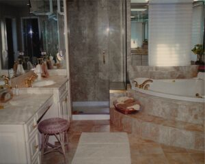 Honed Creme Marfil marble tile and counter tops, Full height mirrored walls, frameless shower enclosure, gold faucets, Hunter Douglas Duette window covering. Elegant contemporary interior design.