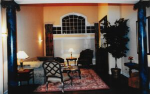 French Quarter inspired decor with clearstory swag and side panel drapery, french Abusson area rug, damask upholstery and faux marble columns. Traditional interior design