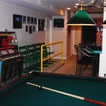 Salvaged Comiskey Park stadium bleacher seating, custom rail, antique juke box, billiard table. Themed interior design