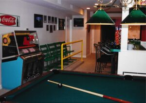 Salvaged Comiskey Park stadium bleacher seating, custom rail, antique juke box, billiard table. Themed interior design