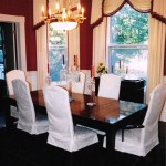 Rich garnet red wall paint, cream damask with garnet hassle trim drapery, cream damask demi-length chair slip covers, Hepplewhite mahogany dining table, brass and milk crystal chandelier. Elegant traditional interior design.