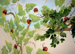 """""""Lady Bug"""" hand painted mural with twig window valance."""