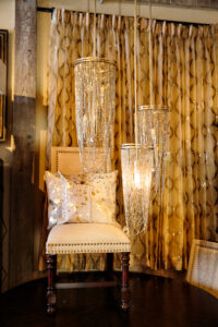 Exceptionally elegant chainmail light pendents with flickering candle bulbs, gold accent hair on hide accent pillows, linen and nail head trimmed dining chairs with a sequin embroidered sheer drapery panels make creating a sensuous interior design.