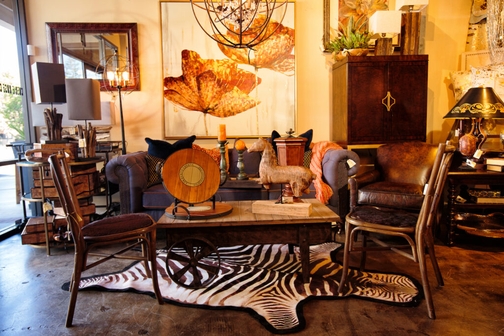 "Transitional interior design is created by using orange poppy and gold embellished wall art, furniture like Lexington bar cabinet, Caracole ""Just Chester"" sofa, hair on hide side chairs, vinyl zebra floor cloth and industrial crystal light pendant."