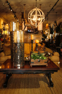 Light and Living geo-globe fixture, oversized black mica mosaic hurricane pedestals, hand painted Casa Bonita treasure box, Lexington bench seat cushion sofa and mahogany scrolled base cocktail table are just some of the furnishings that make up an eclectic interior design.