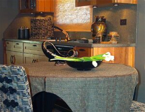 Slip cover table cloth, frog-closure detail on chair reupholstery with coordinating coffee maker cover, cabinet refacing in cherry shaker doors, Corian countertops and full height backsplash, gold and black faucet, woven wood shades. Transitional interior design