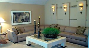 """Custom designed drywall """"wedge"""" detail with rods and sconces, flared arm tight back sectional with coordinating piping to accent pillows, faux maiden grass in distressed Indonesian wash tub, wooden candle pillars on shagreen and glass cocktail table, soft gold leaf accent side table. Contemporary interior design"""